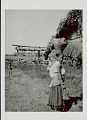 View Woman in Costume and with Ornaments, Carrying Basket on Head And Infant on Back Outside Pole and Mud House with Thatch Roof; Young Boy in Costume and Ping (Gallows-Like Wood Structure Decorated with Wheat for Fertility Feast) Nearby 1965 digital asset number 0