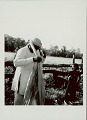 View Man Wrapping Turban Around Head; Young Girl Watching; Both In Costume Near Pole Fence 1965 digital asset number 1