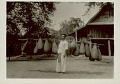 View Man in Costume, Carrying Large Eel Baskets? Outside Bamboo And Plank Platform House with Tile Roof digital asset: Man in Costume, Carrying Large Eel Baskets? Outside Bamboo And Plank Platform House with Tile Roof