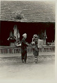 View Man and Woman in Costume and with Headdresses; Woman With Leggings and Carrying Burden Basket with Yoke, Outside Village Shop Selling Baskets, Clothing and Fruit 1931 digital asset number 1