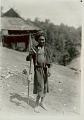 View Boy in Costume with Ornaments and Carrying Parrot Chained To Stick with Perch and Feeding Cups, Outside Bamboo Platform House with Thatch Gabled Roof 1931 digital asset number 1