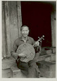 View Man in Costume, Playing Carved Wood String Instrument, Outside Plank House 1931 digital asset number 1