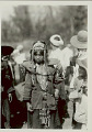 View Woman in Costume with Shell, Bead, and Feather Headdress, And Ornaments, Carrying Burden Basket with Yoke; Group Nearby 1931 digital asset number 0
