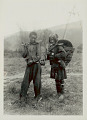 View Man Smoking Pipe and with Woman in Costume and with Ornaments, Carrying Burden Baskets with Yokes on Way to Work in Field 1931 digital asset number 1