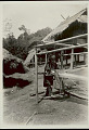 View Woman in Costume and with Ornaments, Weaving on Bamboo Loom With Treadle, Outside Bamboo Platform House with Thatch Gabled Roof 1931 digital asset number 1