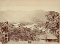 View Two Men in Costume Outside Round Pole and Thatch House Showing Water and Mountainous Landscape in Background 1893 digital asset number 1