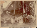View Two Men Wearing Breechcloths Near Three Coral Money Discs Outside Pole Thatch Village Council House on Ceremonial Stone Platform 1893 digital asset number 0
