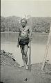 View New Guinea Man Wearing Rattan Fiber Breech-Cloth, Ornaments, Feather Headdress and Holding Spears Near Water 1891 digital asset number 0