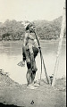 View New Guinea Man in Costume Wearing Braided Palm Fiber Armor, Ornaments, Holding Spear and Near Water 1891 digital asset number 1