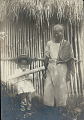 View Woman and Boy with Musical Instrument; Both in Costume Outside Bamboo Frame House with Thatch Roof digital asset: Woman and Boy with Musical Instrument; Both in Costume Outside Bamboo Frame House with Thatch Roof