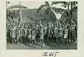 View Large Group of Men in Ceremonial War Costume Outside Pole And Thatch Long Houses 1943 digital asset number 0
