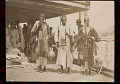 View Three Men, Vendors from Interior of Sierra Leone, in Costume And Selling Spears and Other Goods to Crew on Boat Deck; Group Of Men, Vendors from Syria, in Costume and Selling Clothes Behind Them n.d digital asset number 0