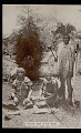 View Bantu Chief with Shield, Spear, and Club and his Two Wives With Shield, Staff, and Switch; All in Costume on Grass Near Bush And Wood Frame House of Town n.d digital asset number 1