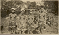 View Four Maidens Wearing White Clay Face Paint and in Costume Near Log Pile and Structure in Field 1926 digital asset number 1