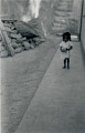 View [Adopted daugher of Manoel, chief drummer at Gantois, holding pot and walking in alley in front of Manoel's house], circa 1938 digital asset number 0