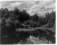 View [Miscellaneous Sites in the Adirondack Mountains]: an unidentified location showing a stream, with a country road going over a small bridge in the background. digital asset: [Miscellaneous Sites in the Adirondack Mountains] [glass negatives]: an unidentified location showing a stream, with a country road going over a small bridge in the background.