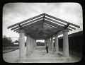 View [Latrobe Park]: workman with rake beneath pergola. digital asset: [Latrobe Park] [lantern slide]: workman with rake beneath pergola.