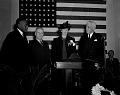 View Secretary Ickes, Secretary [?] McNutt, Mrs. Roosevelt, Dr. T.E. Jones [standing in front of American flag] [black-and-white photonegative] digital asset: untitled