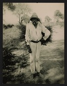 view Unidentified man carrying a bundle of sticks digital asset number 1
