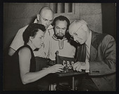 """view Photograph of Irena Brynner showing jewelry to Yul Brynner, Edward G. Robinson, and Cecil B. DeMille on the set of the movie """"The Ten Commandments"""" digital asset number 1"""