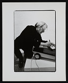 view Photograph of Andy Warhol writing on vacuum cleaner at <em>Art in Process V</em> exhibition digital asset number 1