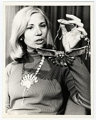 view Arline M. Fisch holding a necklace digital asset: page 1