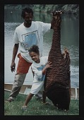 view Photograph of Lonnie Holley and child holding artwork digital asset number 1