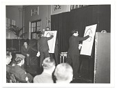 view Abril Lamarque watching two caricaturists on stage digital asset number 1