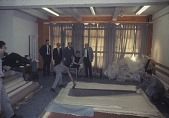 view Michael Fried, Marcella Brenner, Clement Greenberg and others looking at unrolled Morris Louis canvases at Santini Bros. warehouse digital asset number 1