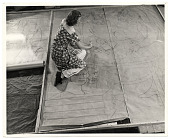 view Photograph of a woman working on a floor mural digital asset number 1