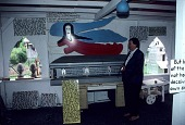 view Jan Rosenak standing next to Howard Finster's casket at Paradise Gardens digital asset number 1