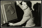 view Katharine Lane Weems posing with the plaque she designed for the Dachshund Club of America's fiftieth anniversary digital asset number 1