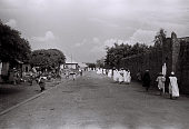 view Field Work in Ilorin, Northern Region (Nigeria): Group of Men, with Traditional Robes and Hats, Walking along Wall of Emir's Palace digital asset: Field Work in Ilorin, Northern Region (Nigeria): Group of Men, with Traditional Robes and Hats, Walking along Wall of Emir's Palace