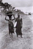 view Field Work in the Floodplains of the Niger and Kaduna Rivers, Northern Region (Nigeria): Nupe Woman Carrying Enamelled Tinware with Flexible Woven Cover and Nupe Man with Mat in Hand digital asset: Field Work in the Floodplains of the Niger and Kaduna Rivers, Northern Region (Nigeria): Nupe Woman Carrying Enamelled Tinware with Flexible Woven Cover and Nupe Man with Mat in Hand