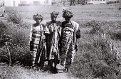 view Field Work in Ibadan, Western Region (Nigeria): Two Women and a Man (probably Yoruba Informants) Wearing Traditional Yoruba Clothes and Headdresses digital asset: Field Work in Ibadan, Western Region (Nigeria): Two Women and a Man (probably Yoruba Informants) Wearing Traditional Yoruba Clothes and Headdresses