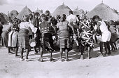 view Field Work on the Benue Plateau, Northern Region (Nigeria): Women Dancing around Musicians Playing Drums on Elevated Wood Platform digital asset: Field Work on the Benue Plateau, Northern Region (Nigeria): Women Dancing around Musicians Playing Drums on Elevated Wood Platform