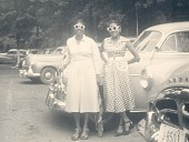 view Mrs. Percival Bryan and friend standing by a car digital asset: Mrs. Percival Bryan and friend standing by a car