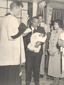 view Percival Bryan holding baby during a religious ceremony digital asset: Percival Bryan holding baby during a religious ceremony