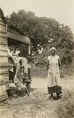 view Gullah woman standing next to her house digital asset: Gullah woman standing next to her house