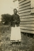 view Katie Groverner [Grovernor] Brown standing next to her house on Sapelo Island, Ga digital asset: Katie Brown [Gullah informant] standing next to her house on Sapelo Island, Ga