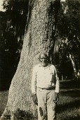 view Gullah man standing by tree digital asset: Gullah man standing by tree