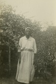 view Gullah woman standing by trees digital asset: Gullah woman standing by trees