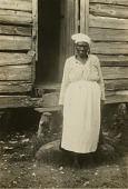 view Gullah woman in front of her house digital asset: Gullah woman in front of her house