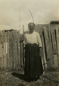 view Gullah woman standing in front of a fence digital asset: Gullah woman standing in front of a fence
