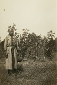 view Gullah woman standing in front of bush digital asset: Gullah woman standing in front of bush