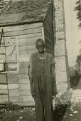 view Bristow McIntosh [Gullah Informant] digital asset: Bristow McIntosh [Gullah informant] standing in front of his house in Harris Neck, Ga
