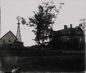 view Distant view of captive balloon with basket over Myers' Balloon Farm. Gates Mansion, windmill, and workshop building in foreground. digital asset: Distant view of captive balloon with basket over Myers' Balloon Farm. Gates Mansion, windmill, and workshop building in foreground.