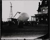 view Unidentified airship envelope is surrounded by crowds at Gates Mansion on Carl Myers' Balloon Farm. Windmill in background. digital asset: Unidentified airship envelope is surrounded by crowds at Gates Mansion on Carl Myers' Balloon Farm. Windmill in background.