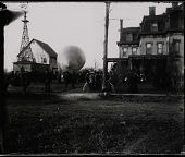 view End view of unidentified airship envelope surrounded by crowds at Gates Mansion on Carl Myers' Balloon Farm. Windmill in background. digital asset: End view of unidentified airship envelope surrounded by crowds at Gates Mansion on Carl Myers' Balloon Farm. Windmill in background.