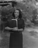 view Outdoor Photo of a Woman Standing Holding Books in her Arms, Rosie Lee Cory digital asset number 1